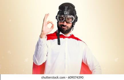 Crazy superhero man making OK sign on ocher background