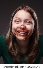Crazy teen grl sitting and laughing with ketchup or blood on her face