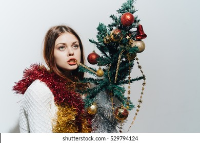 Crazy woman with a Christmas tree in his hand. Crazy drunk lick Christmas tree.