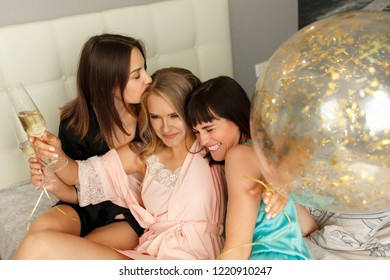 Crazy women party. Photo of laughing, cheerful charming girls at the bridal party, women drinking champagne, playing with balloons. Party concept. Hen-party