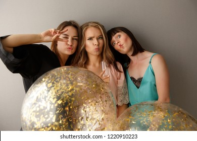 Crazy women party. Portrait of young cute and beautiful girls spending time with fun together while celebrating hen-party at home with balloons. Dressed in silk pajamas.