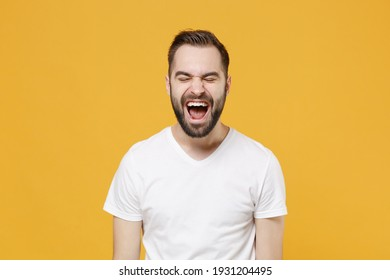 Crazy young bearded man guy in white casual t-shirt posing isolated on yellow background studio portrait. People sincere emotions lifestyle concept. Mock up copy space. Keeping eyes closed, screaming
