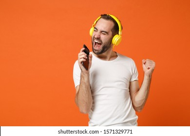 Crazy young man in casual white t-shirt posing isolated on orange background studio portrait. People lifestyle concept. Mock up copy space. Listening music with headphones hold mobile phone sing song