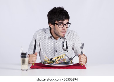 Crazy young man eating technology at his dinner plate