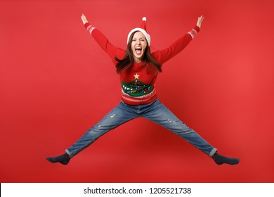 Crazy young Santa girl in Christmas hat jumping, spreading hands and legs, screaming isolated on bright red wall background. Happy New Year 2019 celebration holiday party concept. Mock up copy space