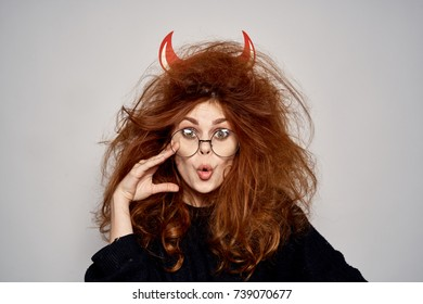 crazy, young woman with horns on a light background, problem with hair