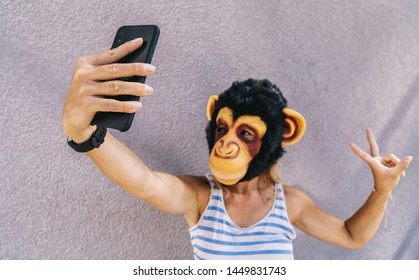 Crazy young woman with monkey mask stands on a gray wall and use a smartphone to take a selfie pic.