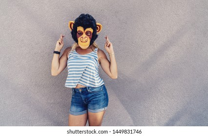 Crazy young woman with monkey mask stands on a gray wall and and cross fingers. copyspace for your individual text.