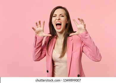 Crazy young woman wearing jacket shouting, growling like animal, making cat claws gesture isolated on pastel pink background in studio. People sincere emotions, lifestyle concept. Mock up copy space