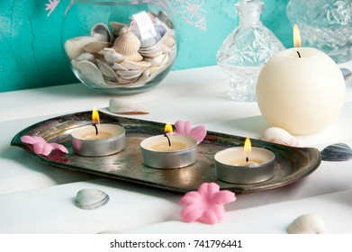 Cream aroma candles and seashelld . Copy space for text.
