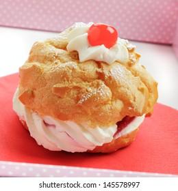 Cream cake with cherries and powdered sugar