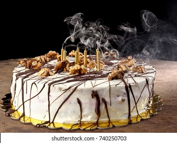 Cream cake with chocolate splash and walnuts and seven blown out candles