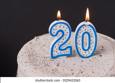 Cream cake with chocolate sprinkles on a vintage white cake stand and number 20 candle on top.  Selective focus on 20