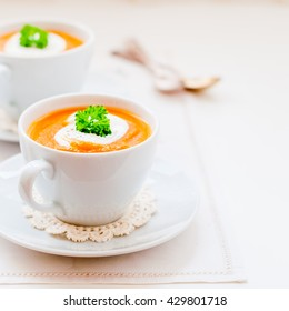 Cream Carrot Soup in a White Cup Garnished with Sour Cream and a Parsley Leaf, square