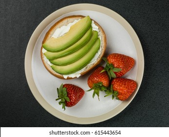 Cream Cheese and Avocado Bagel Against a Black Background