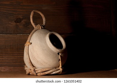 Cream colored birdhouse jug partially wrapped in a twig holder held together with leather straps. With a on a dark wooden board as its background.