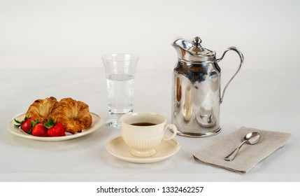 Cream Colored Plate and Coffee Cup with Two Croissants and Three Fresh Strawberries on a White Linen Tablecloth and a Silver Hotel Room Service Carafe with a Napkin and Spoon.