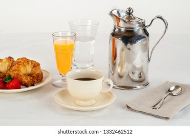 Cream Colored Plate and Coffee Cup with Two Croissants and Three Fresh Strawberries and Orange Juice on a White Linen Tablecloth and a Silver Hotel Room Service Carafe with a Napkin and Spoon.