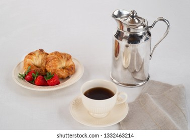 Cream Colored Plate and Coffee Cup with Two Croissants and Three Fresh Strawberries on a White Linen Tablecloth and a Silver Hotel Room Service Carafe with a Napkin.