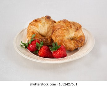 Cream Colored Plate with Two Croissants and Three Fresh Strawberries on a White Linen Tablecloth.