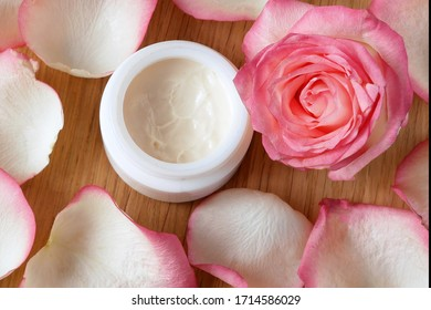 Cream cosmetic in bottle, fresh pink rose flowers and petals, natural cosmetic concept