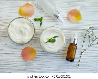 cream cosmetic flower on wooden background moisturizer