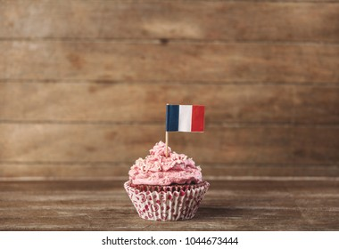 Cream cupcake with franch flag in it on wooden background