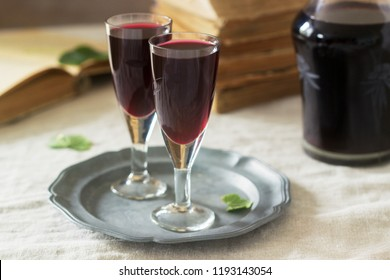Cream de Cassis homemade blackcurrant liqueur in small glasses, books and flowers. Rustic style.