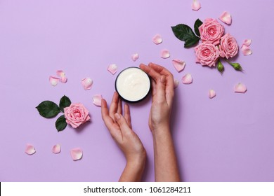 cream and female hands on a pastel background. a composition of flowers, a care cream and hands. minimalism. anti-aging cream. skin care. flatly