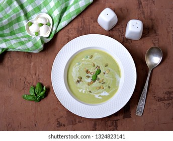 Cream of green pea soup, sprinkled with pumpkin seeds, in a white plate. Served with mozzarella cheese.