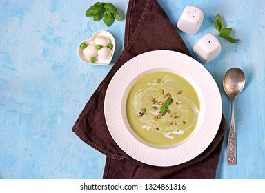 Cream of green pea soup, sprinkled with pumpkin seeds, in a white plate on a blue background. Served with mozzarella cheese. Top view.