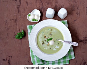 Cream of green pea soup, sprinkled with pumpkin seeds, in a white plate. Served with mozzarella cheese. Top view.