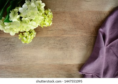 Cream hydrangea and mauve napkin on wood background with room for text in horizontal format