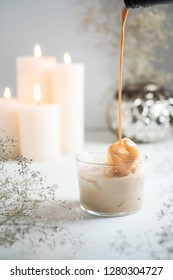 Cream liquor with ice in small glass on a table. Candles and vase with flowers on background.