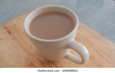 A cream mug of tea standing on kitchen chopping block. In color and monochrome.