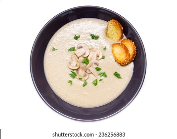 Cream of mushrooms on plate on white background top view