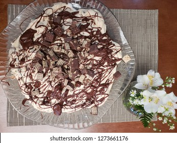 Cream pie with chocolate biscuit called bis and table decorated with flower pot.