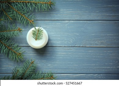 Cream and pine branches on wooden background