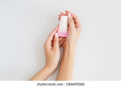 cream in a pink tube in woman's hands. Small bottle with cosmetic. Face care product. Personal care. Female beauty. Face tonic, face serum, eye cream