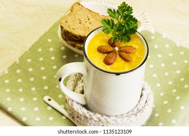 Cream of pumpkin soup with parsley and almonds. A traditional autumn dish. Top view.