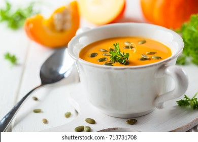 Cream of pumpkin soup with pumpkin seeds on white cutting board
