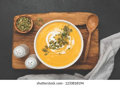 Cream of pumpkin soup in white bowl on wooden serving board, top view
