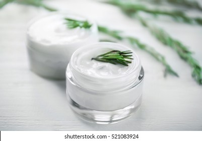 Cream and rosemary on wooden background