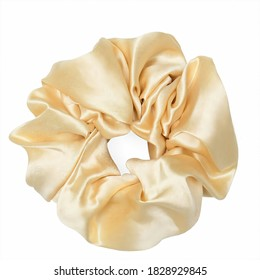 A cream scrunchie that is in the shape of a circle, as well as a scrunchie placed on a white table.