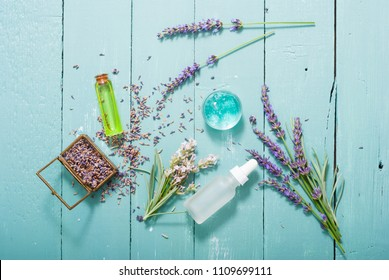 cream, shampoo, perfume product samples with lavender on old blue wood table background