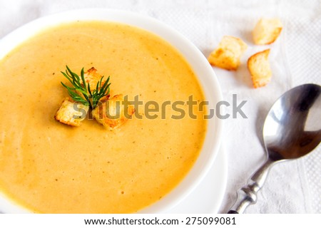 Cream soup with croutons and dill  on white napkin, horizontal close up