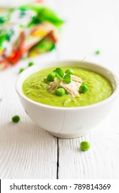 Cream soup of green peas in a white plate on a white wooden background
