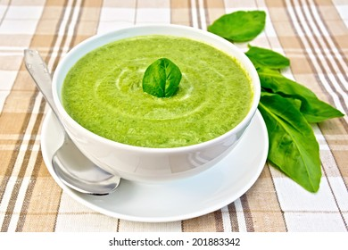 Cream soup green from spinach in a white bowl and saucer, spoon on the background fabric