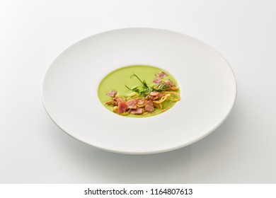 cream soup with greens and bacon isolated on white background.