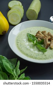 Cream soup of mashed potatoes with zucchini and basil and crackers on a dark background.